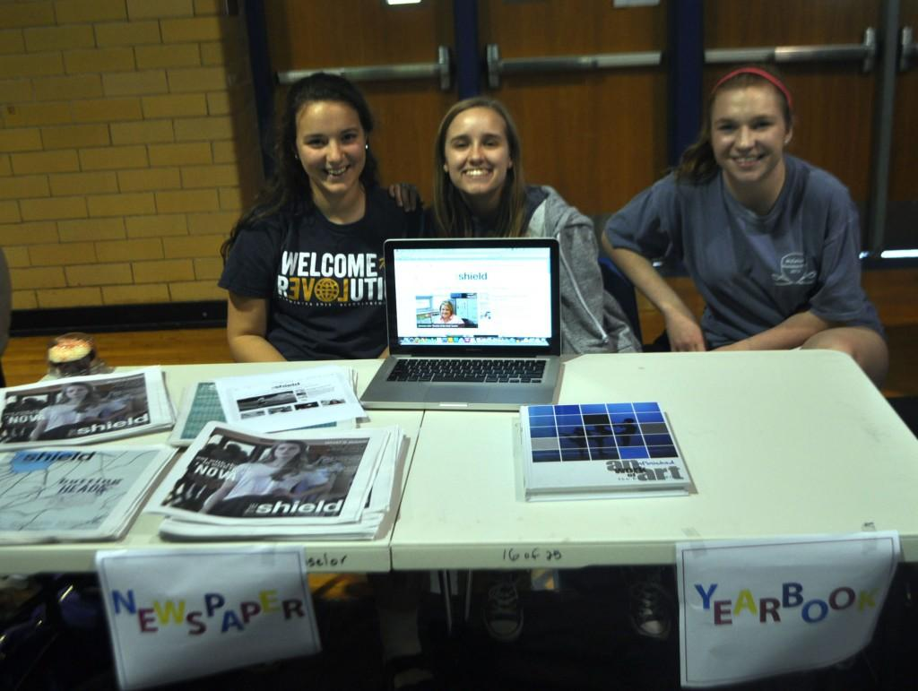 Staffers Natalie Murphy, Hegefeld, and Mara Vandegrift work at the elective fair.
