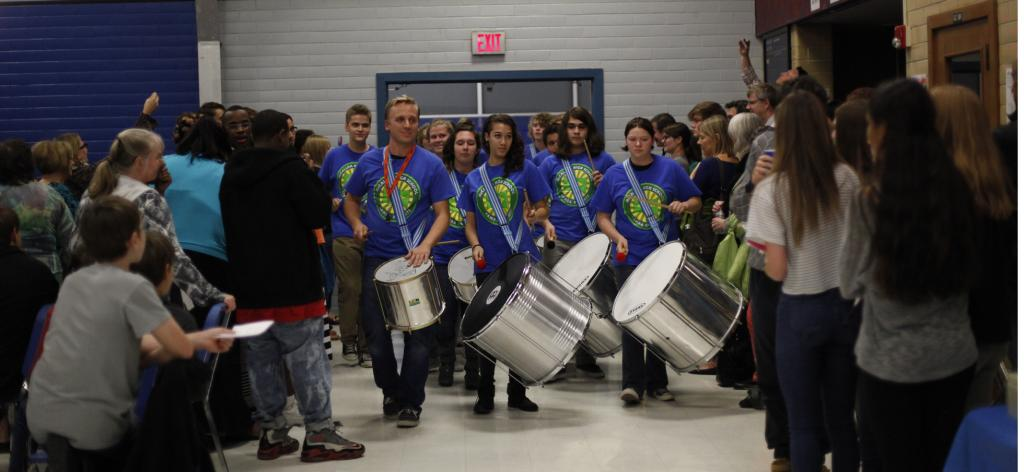 Percussion teacher Matt Ehlers leads the Samba Knights in its procession into the cafeteria for a performance at the annual Knights of Steel dessert concert Nov. 24. The group played some of their sets for students at lunch last week in addition to at the concert. Photo by Aiden Foster.