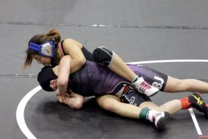 McCallum wrestling team captain, Adriana Boortz, leads by example for her fellow wrestlers as she keeps the upper-hand against LBJ's 102-pounder. Boortz eventually pinned her opponent during the second round en route to defending her district title. Photo by Beth Bishop