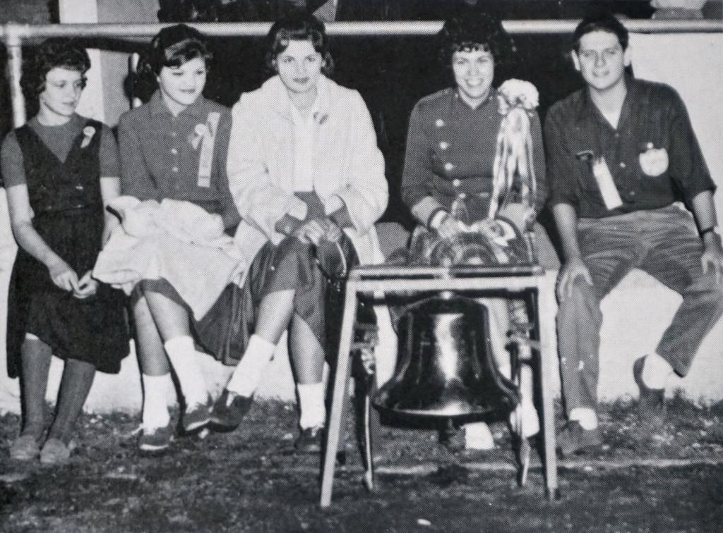 """Caesar had his Brutus, Napoleon his Waterloo, and Travis -- the McCallum game,"" reads the caption in the 1962 Knight. ""The victory bell, purchased by the publications by the publications departments of Travis and McCallum, is guarded by editors from both schools: Judy Calvert, Janet Barkley, and Carolyn Barkley of Travis, and Gwen Chancellor and Bill Towery of McCallum."" Photo from the 1962 Knight."