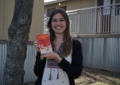 Ms. Olson poses with a copy of Catcher in the Rye. Photo by Madison Olsen