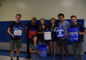 PALS members, Cristain Miranda, Atley Brown, Alana Raper, Charlie Holden, Noah Savage, Eric LaWare and Sam Stone, pose outside Mr. Cowles' room with the five-gallon buckets they used to collect donations during the shower strike. Photo by Gregory James.