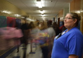"LEFT: Officer Georgia Gonzalez watches as students pass through the main hallway during passing period. ""I really like interacting with the students as they go to class."" Gonzalez said.  Photo by Gregory James."