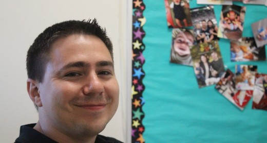 Mr. Schuler poses in his classroom in front of pictures of his son. Photo by Amurri Davis.