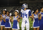 PINKIE PROMISE: Max Perez joins cheerleaders Daejha Taylor, Robyn McCray, Lily Ponce, Lina Coleman, Miles Perkins hold pinkies and sing the school song after the McCallum victory versus Lehman. Photo by Zoe Hutchens.