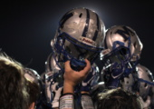 HARD HATS: In the final post-game huddle, players raise their battered helmets to the sky. Photo by Ian Clennan