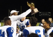 ON TO THE NEXT ONE: Coach Charles Taylor raises the Bi-district trophy  for the football team. The Knights won the game against Medina Valley 37-14. Photo by Gregory James