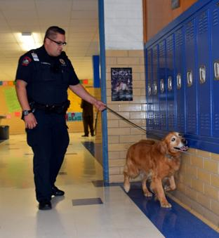 Campus police officer Anthony Andrews walks Rocco the drug dog down the hallway to search the lockers. Read more about Rocco in the upcoming issue of The Shield March 13.