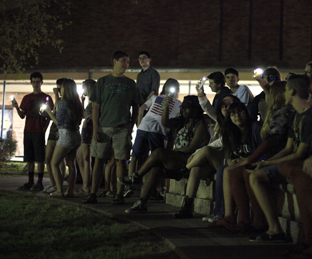 Listeners gather in the courtyard where student bands are playing at the Spring into Music band fundraiser. Photo by Aiden Foster.